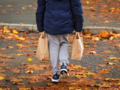 A child collects packed lunch bags for the holidays (Peter Byrne/PA)