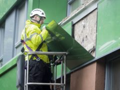A workman removes cladding from a tower block (Danny Lawson/PA)