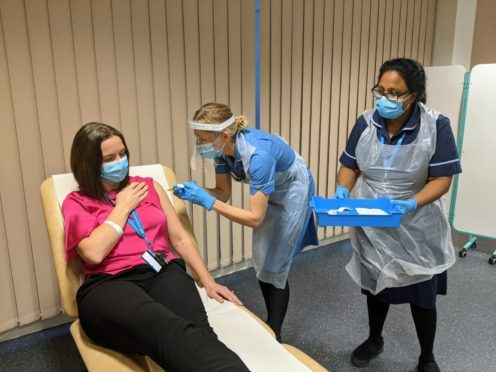 Dr Claire Cole, head of research delivery at MFT, receives a dose of the vaccine developed by Janssen after she became the first volunteer for the phase three trial (Manchester University NHS Foundation Trust/PA)