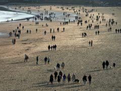 People walking on a beach (Owen Humphreys/PA)