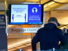 An electronic sign advises travellers to wear face masks and practice social distancing while passing through the main terminal of Denver International Airport (David Zalubowski/AP)