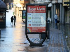 Shoppers in Nottingham city centre walk past a coronavirus advice sign (Mike Egerton/PA)