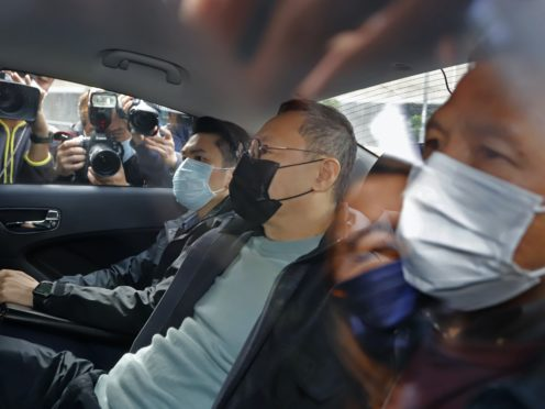 Former law professor Benny Tai sits in a car after being arrested by police in Hong Kong (Apple Daily/AP)