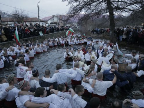 Dozens of citizens of the mountain town of Kalofer, in central Bulgaria, clad in traditional clothes stand in the icy Tundzha River (Valentina Petrova/AP)