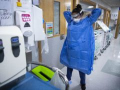 A staff nurse puts on PPE in the corridor of the Acute Dependency Unit at St George's Hospital in Tooting, south-west London (Victoria Jones/PA)
