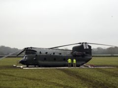 Personnel from the Joint Aircraft Recovery and Transportation Squadron next to the Chinook (Steve Parsons/PA)
