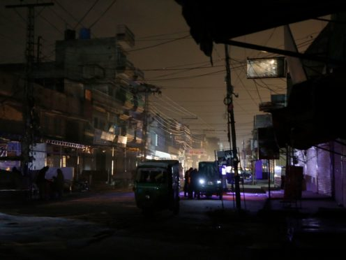 People and rickshaws are silhouetted in vehicles' headlights on a dark street in Rawalpindi during a widespread power cut in Pakistan (Anjum Naveed/AP)