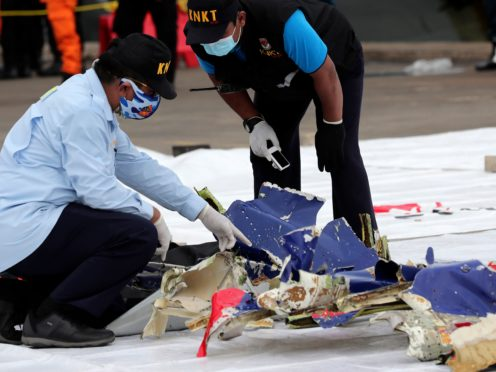 Officials from the Indonesian National Transportation Safety Committee inspect parts of Sriwijaya Air Flight 182 retrieved from the java Sea (Tatan Syuflana/AP)