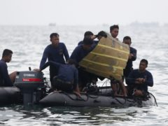 Indonesian Navy divers pull a part of an airplane out of the water during a search operation for the Sriwijaya Air passenger jet that crashed into the sea near Jakarta, Indonesia (Achmad Ibrahim/AP)