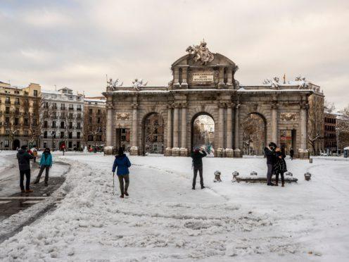 People walk through snow in Madrid's Puerta de Alcala square (Manu Fernandez/AP)