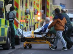 Paramedics and hospital staff attend to a patient outside the Royal London Hospital in London (Yui Mok/PA)