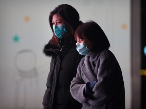 People wearing face masks to protect against the spread of the coronavirus in Beijing (Mark Schiefelbein/AP)