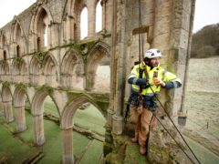 Stonemason James Preston from SSH Conservation surveys Rievaulx Abbey in North Yorkshire (Danny Lawson/PA)