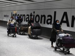 Passengers push luggage through the Arrival Hall of Terminal 5 at Heathrow (Kirsty O'Connor/PA)