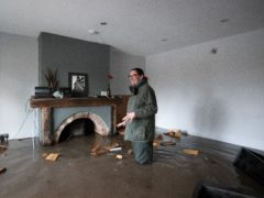 Gabrielle Burns-Smith looks out from her flooded home on the outskirts of Lymm (Joe Giddens/PA)