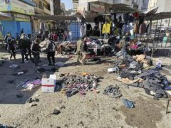 People and security forces gather at the site of a deadly bomb attack in a market selling used clothes in Iraq (Hadi Mizban/AP)