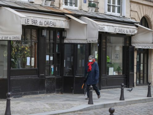 A woman wearing face a mask as a precaution against the coronavirus walks past a closed restaurant in Paris (Michel Euler/AP)