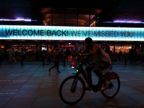 A cyclist riding past a sign saying 'Welcome Back! We've Missed You' displayed above the front of the BFI Southbank (Yui Mok/PA)