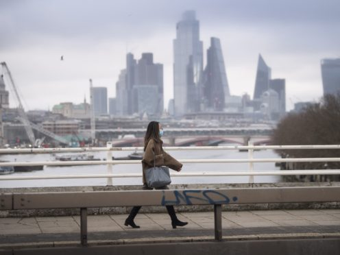 A lone woman wearing a facemask walks over an empty Waterloo Bridge (PA)