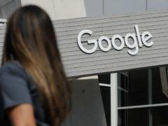 A woman walks below a Google sign (AP)