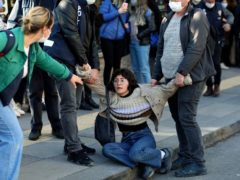 A woman reacts as riot police officers detain a student during a protest in Ankara (AP)