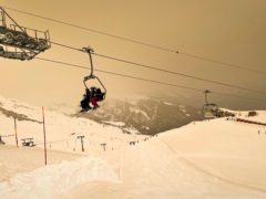 Skiers wearing protective face masks sit on a chairlift as Sahara sand colours the snow and the sky in orange and creates a special light atmosphere in the Alpine resort of Anzere, Switzerland (Laurent Gillieron/Keystone via AP)