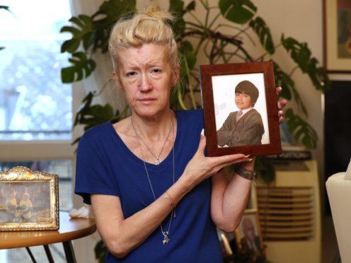 Jasna Badzak holding a 2014 photograph of her son Sven (Jonathan Brady/PA)