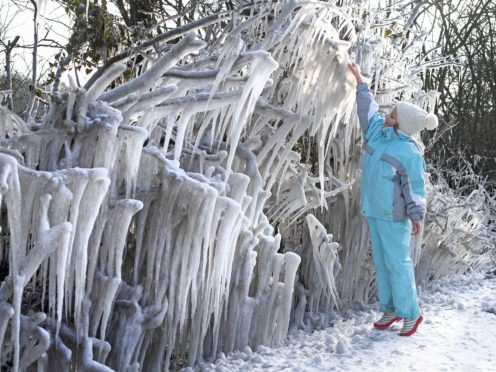 Christina Staucean, seven, reaches to touch giant icicles formed in Epping Forest (Victoria Jones/PA)