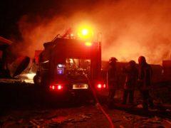 Firefighters work on a burning tanker carrying fuel (Hamed Sarfarazi/AP)