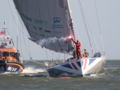 Pip Hare sets off a flare as she sails her boat Medallia into Poole (PA)