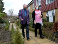 Tom Jones, 103, walks laps of the garden at his care home in Bexleyheath, Kent, with activity co-ordinator Debbie Rutty (Gareth Fuller/PA)