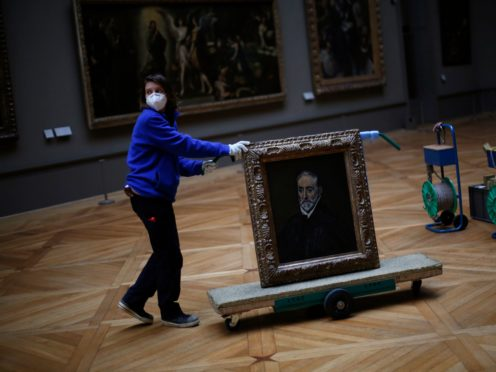 A worker transports the painting called Portrait of Antonio de Covarrubias y Leiva by Spanish painter El Greco in the Louvre museum in Paris (Thibault Camus/AP)