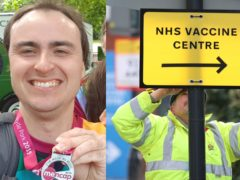 Mencap ambassador Harry Roche, who has a learning disability, and a Brent Council worker hangs a direction sign to the NHS Covid Vaccine Centre at the Olympic Office Centre, Wembley (Harry Roche and Yui Mok/PA)
