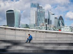 A man sits and eats alone in the sun at lunchtime near City Hall, in central London (Dominic Lipinski/PA)