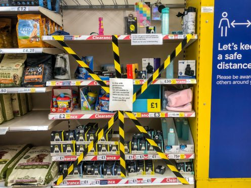 Some shelves in supermarkets were taped off to stop customers buying items deemed to be non-essential (Ben Birchall/PA)