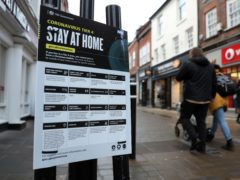 People make their way past a Government coronavirus sign (PA)