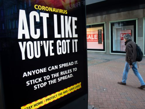 A person passes an 'Act like you've got it' coronavirus sign on Old Christchurch Road in Bournemouth (Andrew Matthews/PA)