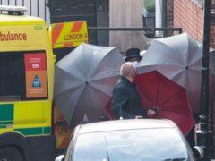 Staff shield the exit with umbrellas alongside an ambulance outside King Edward VII's Hospital (Dominic Lipinski/PA)