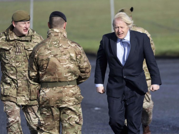Prime Minister Boris Johnson greets troops alongside Brigadier Chris Davies, Commander 38 (Irish) Brigade (left), during a visit to Joint Helicopter Command Flying Station Aldergrove in Northern Ireland. Picture date: Friday March 12, 2021.
