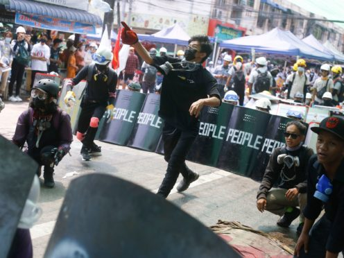 Anti-coup protesters practise a defence formation with makeshift shields during a demonstration in Yangon, Myanmar (AP)