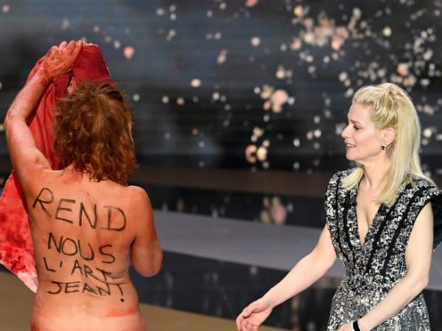 French actress Corinne Masiero, left, removes her costume on stage alongside host Marina Fois at the 46th Cesar Award ceremony (AP)