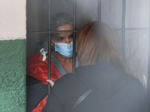 Standing behind bars, Bolivia's former interim President Jeanine Anez speaks to an unidentified woman at a police station jailhouse, in La Paz (Juan Karita/AP)