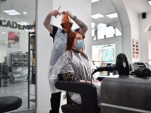 Senior stylist Robert Brooks cuts the hair of Carmen Smith at the Lazarou salon in Cardiff, Wales (Ben Birchall/PA)