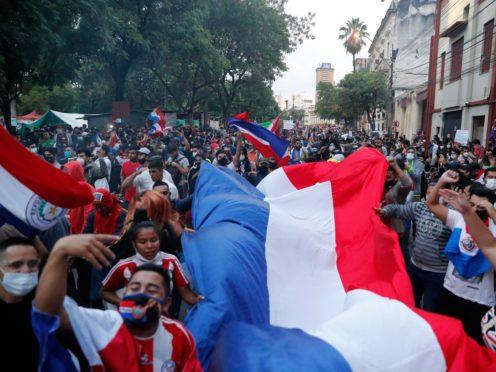 Demonstrators carry a Paraguayan flag during a protest after a failed impeachment of President Mario Abdo Benitez, in Asuncion, Paraguay (Jorge Saenz/AP)