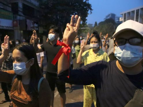 Anti-coup protesters flash three-fingered gesture, a symbol of resistance, during a rally outside their homes in downtown Yangon, Myanmar (AP)