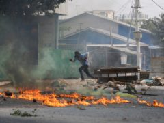 A man runs past a road barricade and burning debris Monday, March 22, 2021, in Mandalay, Myanmar. The BBC said Monday that a journalist from its Burmese-language service was released by authorities in Myanmar but gave no details, as protesters in the Southeast Asian nation continued their broad civil disobedience movement against last month's military coup. (AP Photo)
