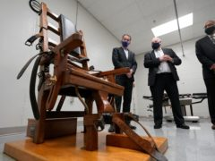 Virginia governor Ralph Northam, left, looks over the electric chair in the death chamber at Greensville Correctional Centre with Operations Director, George Hinkle, center, and Warden Larry Edmonds, right, prior to signing a bill abolishing the death penalty (Steve Heiber/AP)