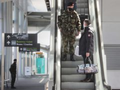 A passenger is escorted to a coach by a member of the Defence Forces after arriving at Dublin Airport (Brian Lawless/PA)