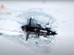 In this handout photo taken from a footage released by Russian Defense Ministry Press Service on March 26, 2021, A Russian nuclear submarine breaks through the Arctic ice during military drills at an unspecified location. Russian President Vladimir Putin on Friday hailed the military's performance during recent Arctic drills, part of Moscow's efforts to expand its presence in the polar region. (Russian Defense Ministry Press Service via AP)