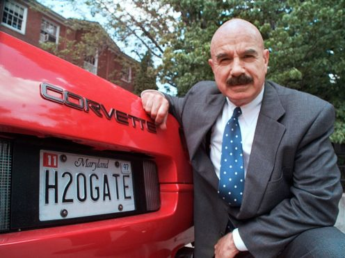 G Gordon Liddy kneels next to his Corvette in this 1997 photo (Ron Edmonds/AP)